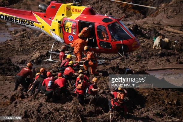 TOPSHOT A helicopter provides support to the work of rescuers and firefighters in the search for victims four days after the collapse of a dam at an...