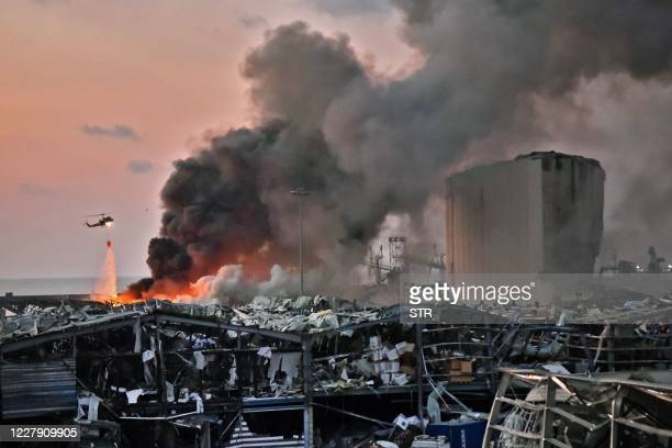 Helicopter puts out a fire at the scene of an explosion at the port of Lebanon's capital Beirut on August 4, 2020.