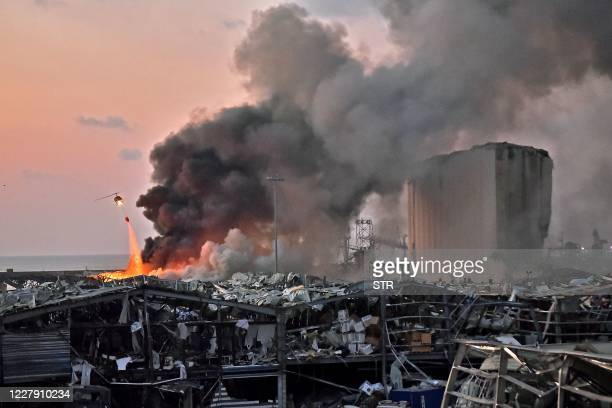 A helicopter puts out a fire at the scene of an explosion at the port of Lebanon's capital Beirut on August 4 2020