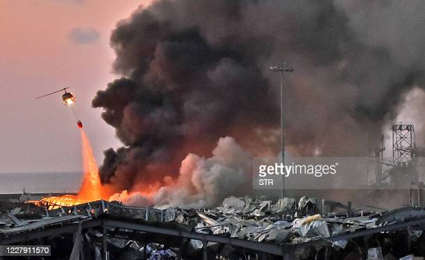 TOPSHOT A helicopter puts out a fire at the scene of an explosion at the port of Lebanon's capital Beirut on August 4 2020