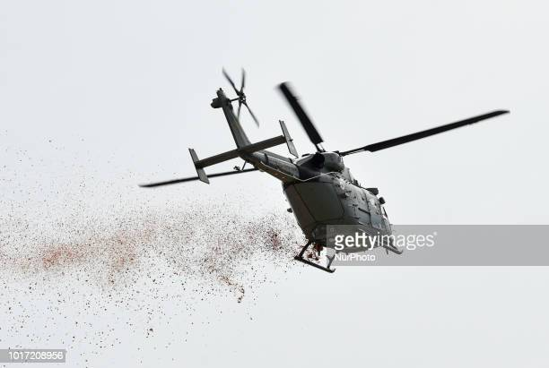 A helicopter showers flower petals during the 72nd Independence Day celebrations at Khanapara Veterinary College playground in Guwahati Assam India...
