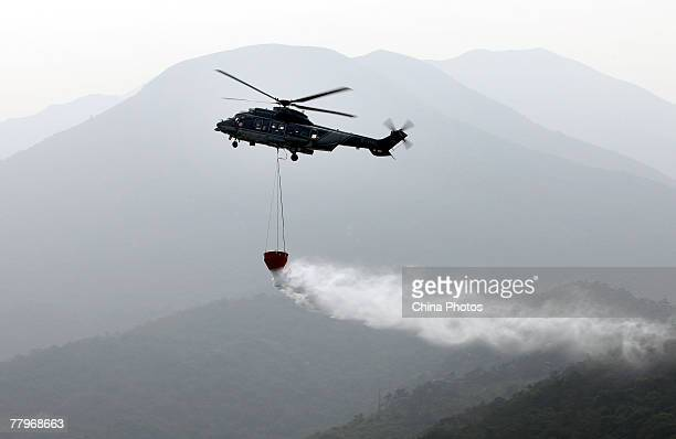 A helicopter sprays water to put out a fire in a demonstration during the Government Flying Service Open Day on November 18 2007 in Hong Kong China...