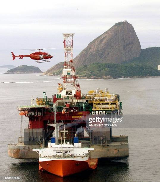 A helicopter surveys the oildrilling platform P36 of the Brazilian stateowned oil company Petrobras as it arrives on board a freighter in the...