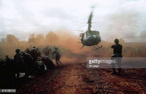 A US helicopter takes off from a clearing near Du Co SF camp Vietnam Wounded soldiers crouch down in the dust of the departing helicopter The...