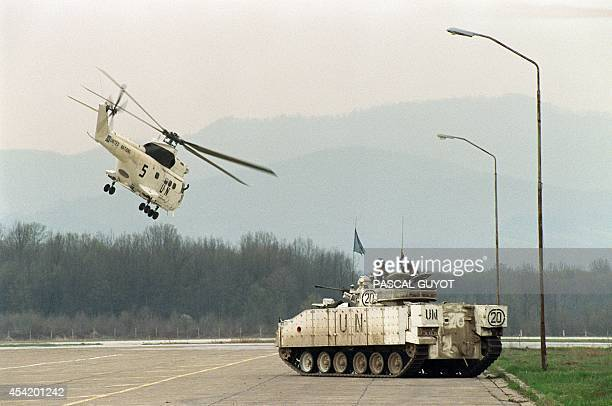 Helicopter takes off near a UN Canadian tank 17 April 1993 at Tuzla's airport before their depart for the Moslem enclave of Srebrenica where some...