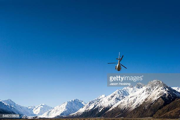 helicopter taking off with heliskiers - helicopter stock pictures, royalty-free photos & images