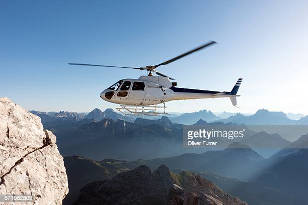 Helicopter transporting BASE jumpers to summit, Dolomites, Italy