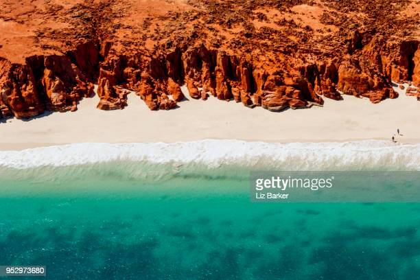 a helicopter view of the white sands, turquoise ocean and striking red kooljaman cliffs at cape leveque in western australia's north west. - landscape stock pictures, royalty-free photos & images