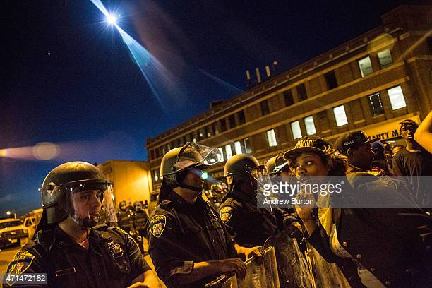 A helicopter with a spot light watches over police and protesters before a mandatory citywide curfew of 10 pm near the CVS pharmacy that was set on...
