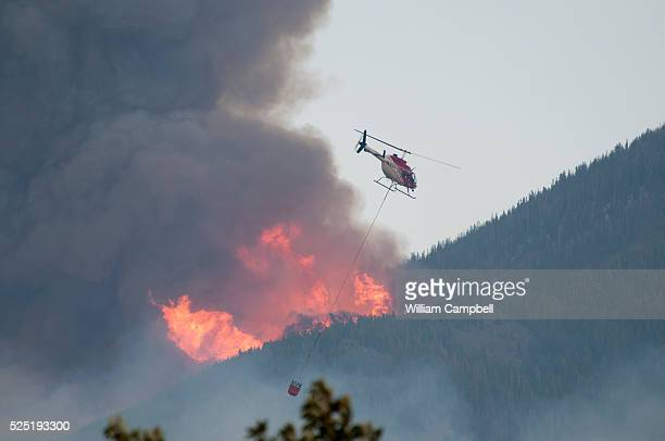 A helicopter with a water bucket passes below torching on the ridge above Pine Creek Montana while battling the Pine Creek fire 9 miles south of...