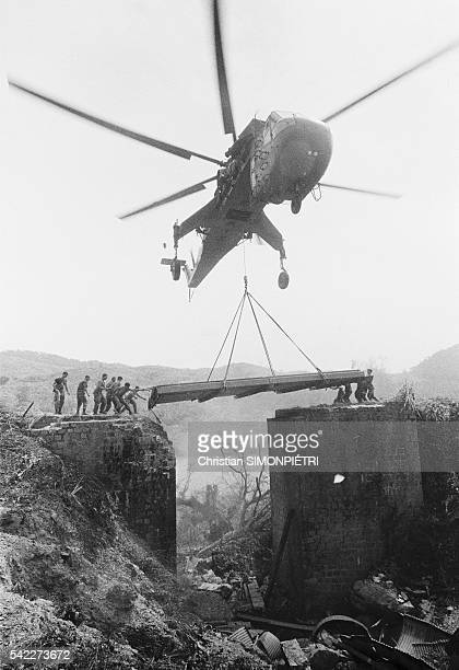 A helicopter with the First US Airborne Cavalry Division repairs a destroyed bridge in Khe Sanh for the crossing of troops as a part of Operation...