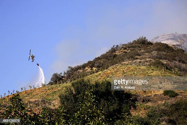 A helicopter works to control wildfires as they burn through hillsides on January 16 2014 in Azusa California Authorities have stated that three...