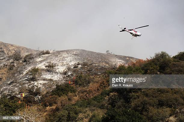 Helicopters and fire emergency services work to control the wildfires as they burn through hillsides on January 16 2014 in Azusa California...