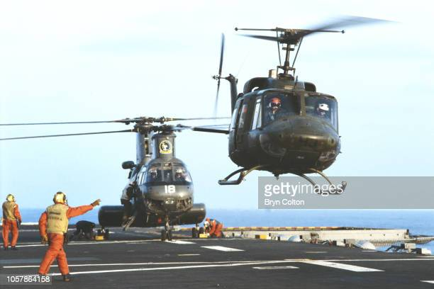 Helicopters are waved off by a crew member from the flight deck of the USS Saipan a Tarawaclass amphibious assault ship of the United States Navy...