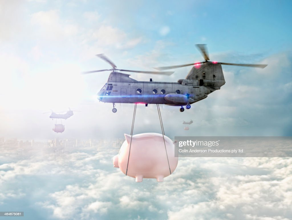 Helicopters carrying piggy banks over clouds : Stock Photo