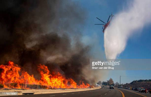Helicopters drop water after inmate crews set backfires to heavy brush along Madera Rd as firefighters try to keep the Easy fire from crossing the...
