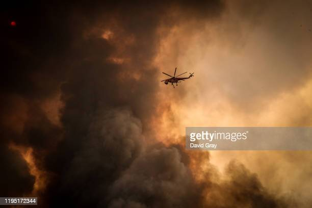 Helicopters dump water on bushfires as they approach homes located on the outskirts of the town of Bargo on December 21 2019 in Sydney Australia A...