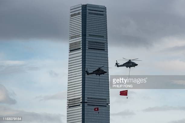 Helicopters fly across Victoria Harbour carrying a Hong Kong and China flag during the annual flag raising ceremony to mark the 22nd anniversary of...