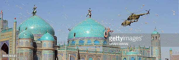 Helicopters fly over the Hazrat Ali Shrine in MazariSharif on March 20 2009 Tens of thousands of Afghans from all over the warscarred country have...