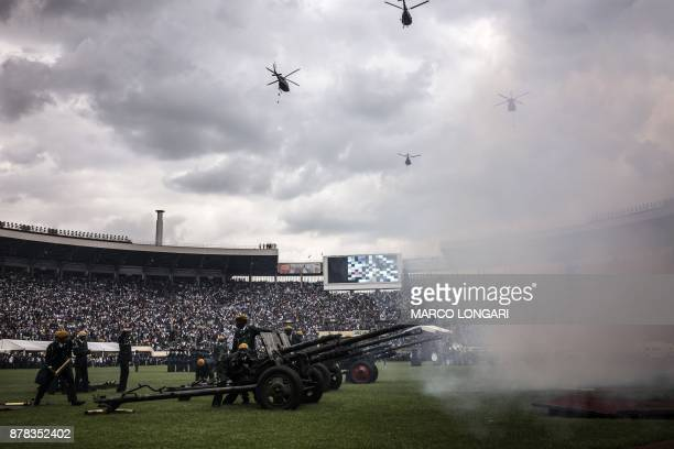 Helicopters fly over the National Sport Stadium in Harare on November 24 2017 as a battery of artillery fires salvos during the Inauguration ceremony...