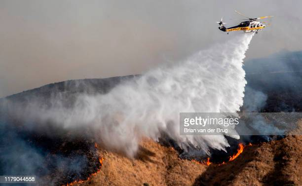 Helicopters hit flames and burning brush along Madera Rd as firefighters battle the Easy fire October 30 2019 in Simi Valley California Fueled by the...