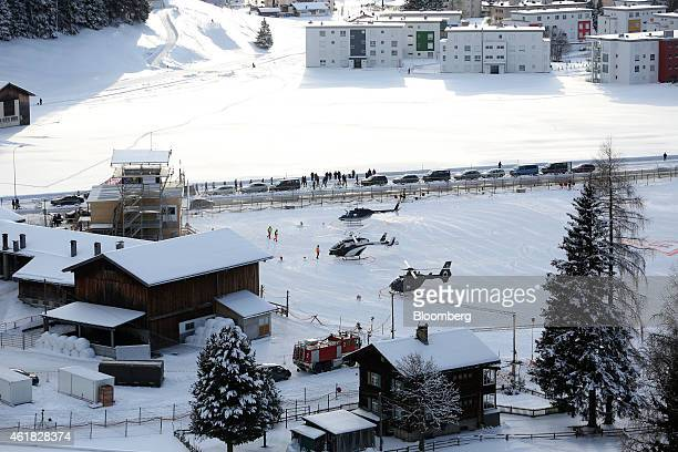 Helicopters stand in the snow on the helipad at the InterContinental Hotel Davos operated by InterContinental Hotels Group Plc ahead of the World...