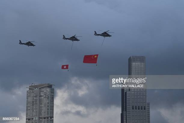 Helicopters towing the flags of China and Hong Kong fly over Victoria Harbour during a flag raising event to celebrate China's national day in Hong...