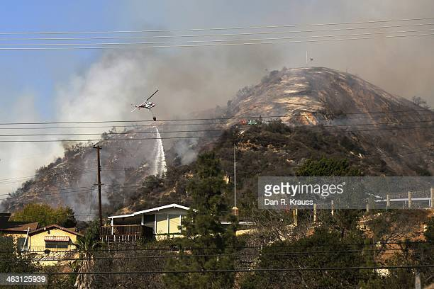 Helicopters work to control the wildfires as they burn through the hillsides on January 16 2014 in Azusa California Authorities have stated that...