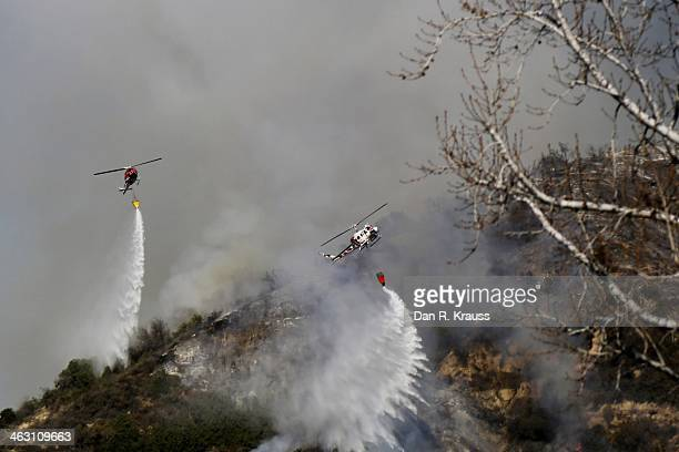 Helicopters work to control wildfires as they burn through hillsides on January 16 2014 in Azusa California Authorities have stated that three people...