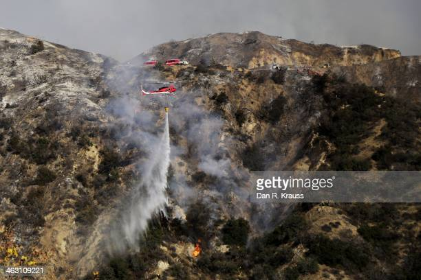 Helicopters work to control wildfires as they burn through the hillsides on January 16 2014 in Azusa California Authorities have stated that three...