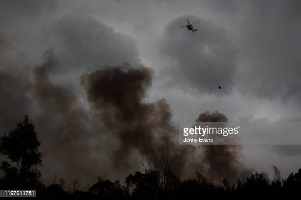 Helicpter water bombs a fire at Voyager Point in western Sydney on January 05, 2020 in Sydney, Australia. One person has died overnight in Batlow and...