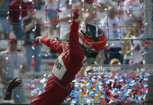 Helio Castroneves climbs the fence to celebrate his win in the IRL IndyCar Series Emerson Indy 250 on August 10 2003 at the Gateway International...