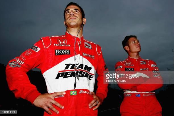 Helio Castroneves driver of the Team Penske Dallara Honda and team mate Ryan Briscoe driver of the Team Penske Dallara Honda wait on pit road prior...