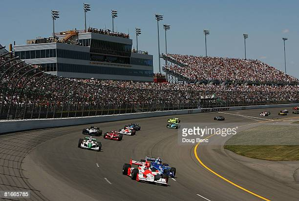 Helio Castroneves drives the Team Penske Dallara Honda past Scott Dixon driver of the Target Chip Ganassi Racing Dallara Honda through turn one...