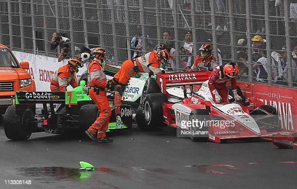 Helio Castroneves of Brazil climbs from the Itaipava Team Penske Dallara Honda after a crash involving Danica Patrick driver of the Andretti...