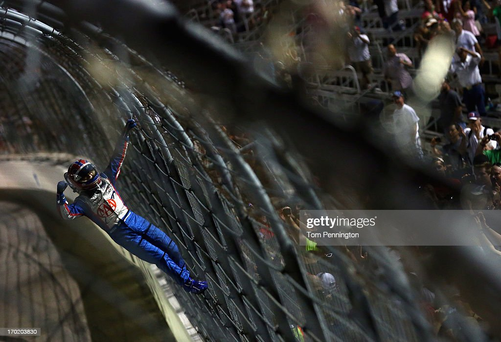 Helio Castroneves of Brazil, driver of the #3 AAA Insurance Team Penske Chevrolet, celebrates by climbing the fence on the front stretch after winning the IZOD IndyCar Series Firestone 550 at Texas Motor Speedway on June 8, 2013 in Fort Worth, Texas.