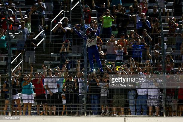 Helio Castroneves of Brazil, driver of the AAA Insurance Team Penske Chevrolet, celebrates by climbing the fence on the front stretch after winning...