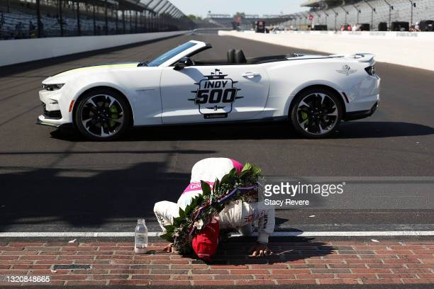 Helio Castroneves of Brazil, driver of the AutoNation/SiriusXM Meyer Shank Racing Honda, celebrates by kissing the yard of bricks after winning the...
