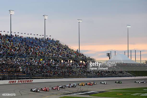 Helio Castroneves of Brazil driver of the HItachi Team Penske Dallara Chevrolet leads a pack of cars during the Iowa Corn Indy 300 at Iowa Speedway...