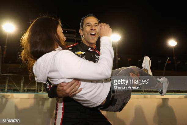 Helio Castroneves of Brazil driver of the Team Penske Chevrolet celebrates with girlfriend Adriana Henao after winning the Verizon P1 Pole Award for...