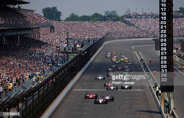Helio Castroneves of Brazil driver of the Team Penske Dallara Honda leads the field at the start of the IZOD IndyCar Series 94th running of the...