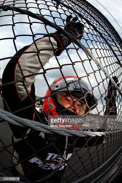 Helio Castroneves of Brazil driver of the Team Penske Dallara Honda celebrates by climbing the fence after winning the IZOD IndyCar Series Indy Japan...