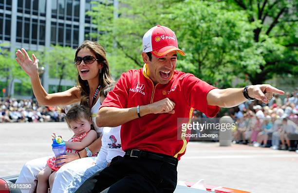Helio Castroneves of Brazil driver of the Team Penske Dallara Honda with his girlfriend Adriana Henao and his daughter Mikaella waves to the crowd...