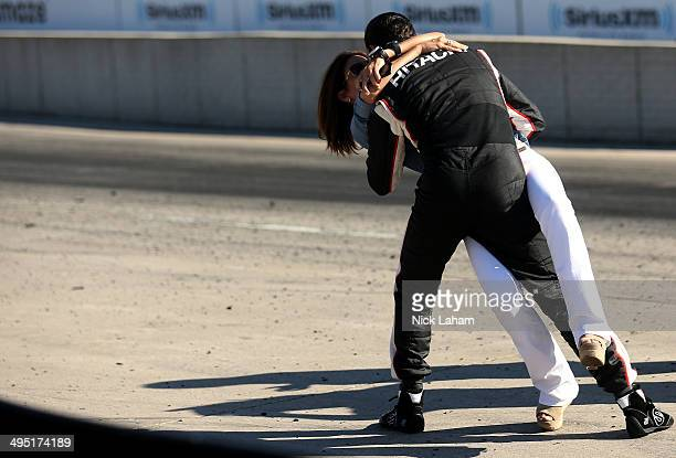 Helio Castroneves of Brazil driver of the Team Penske Dallara Chevrolet celebrates winning with girlfriend Adriana Henao the Verizon IndyCar...
