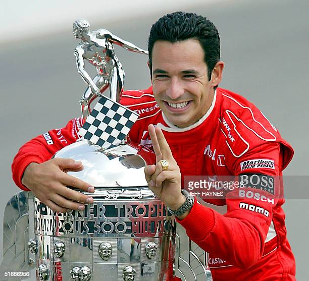 Helio Castroneves of Brazil hugs the BorgWarner trophy during a photo session after winning his second race in a row 27 May 2002 in the 86th running...