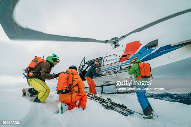 heli-skiers disembark from helicopter, on snow crest - kaukasus geografische lage stock-fotos und bilder