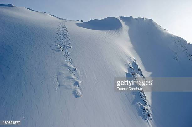 heliskiers on a steep face. - back country skiing stock pictures, royalty-free photos & images