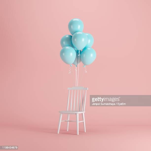 helium balloons tied to chair against colored background - balloon stock pictures, royalty-free photos & images