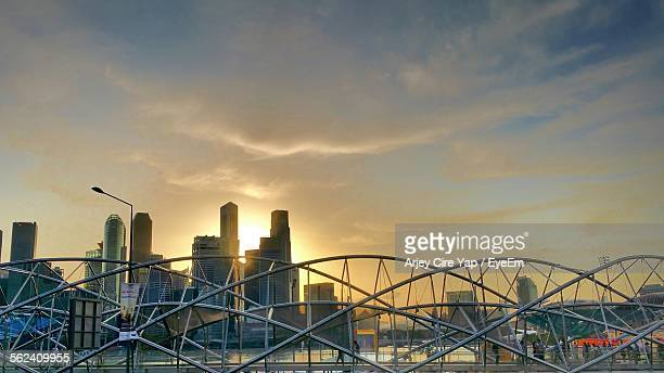 Helix Bridge And Buildings Against Cloudy Sky During Sunset