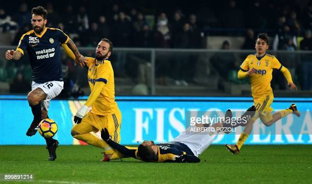 Hellas Verona's Italian defender Antonio Caracciolo fights for the ball with Juventus's forward from France Gonzalo Higuain C flanked by Hellas...